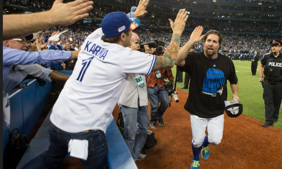 Toronto Blue Jays' R.A. Dickey celebrates with fans after winning  Game 5 of baseball's American League Division Series against the Texas Rangers, Wednesday, Oct. 14, 2015, in Toronto. The Blue Jays clinched their first trip to the American League Championship Series since 1993, overcoming one of the most bizarre plays in playoff history by taking advantage of three Rangers errors for a 6-3 victory.  (Chris Young/The Canadian Press via AP) MANDATORY CREDIT ORG XMIT: CHY201