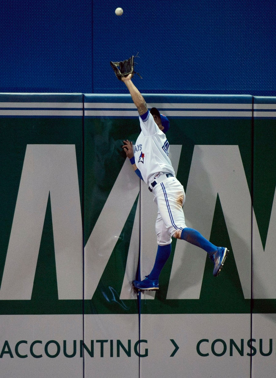 Toronto Blue Jays left fielder Kevin Pillar makes a catch on the other side of the wall hit by Tampa Bay Rays Tim Beckham during the seventh inning of a baseball game, Wednesday, April 15, 2015 in Toronto. (Nathan Denette/The Canadian Press via AP)  MANDATORY CREDIT ORG XMIT: NSD113